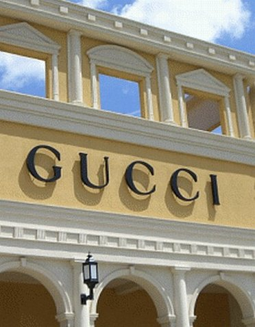 Close up of a Gucci Outlet Stores sign